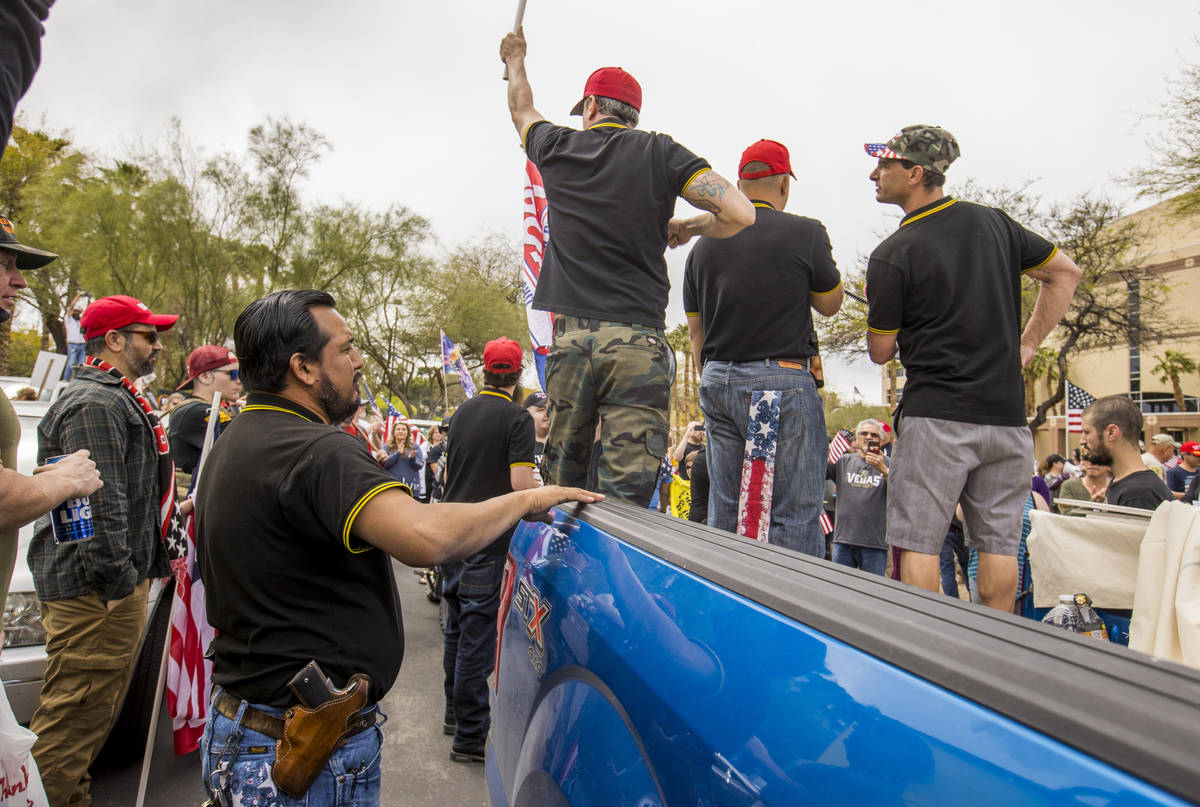 Proud Boys stand atop of a truck and welcome all to enter as Reopen Nevada holds a protest agai ...