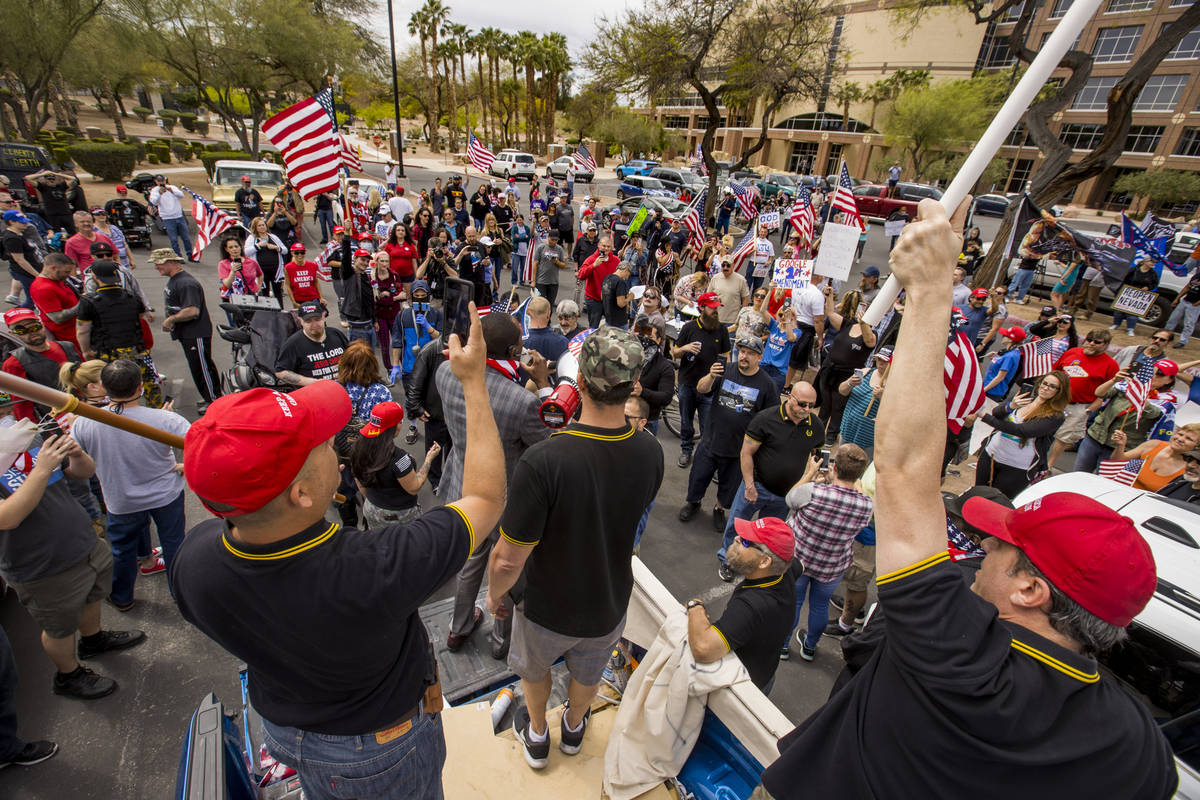 Proud Boys speak and stand atop of a truck during a Reopen Nevada protest against Gov. Steve Si ...