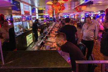 People gamble and order drinks at a bar in the Fremont Hotel and Casino after casinos reopened ...