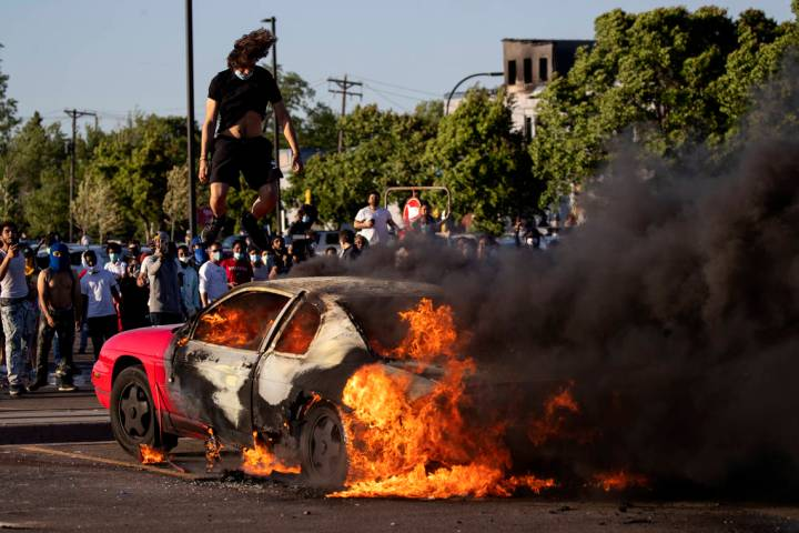 A car burns in a Target parking lot Thursday, May 28, 2020, in Minneapolis. Minnesota Gov. Tim ...