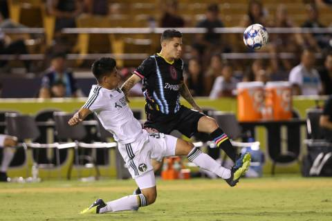 Las Vegas Lights' Raul Mendiola (40) fights for the ball against Portland Timbers' Marco Farfan ...