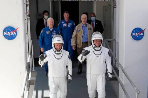 NASA astronauts Douglas Hurley, left, and Robert Behnken walk out of the Neil A. Armstrong Oper ...