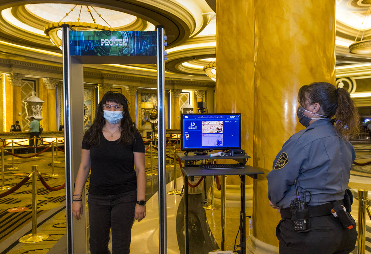 Asuka Anderson, left, walks through the infrared thermal scanner for temperature readings opera ...
