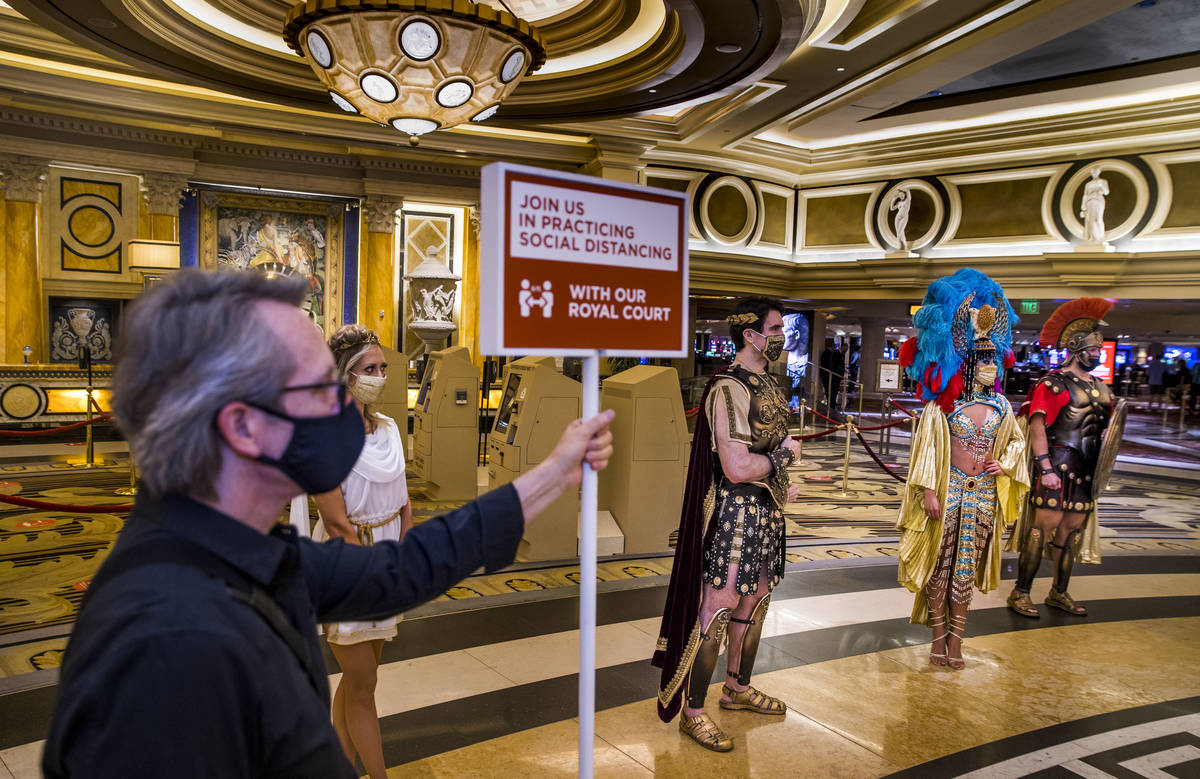 A social distancing sign helps to announce the royal court with Caesar and Cleopatra as part of ...