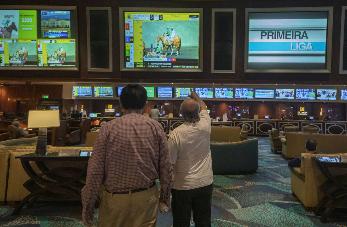 Individuals wait for a horse race to begin during the reopening of the Bellagio sportsbook, Thu ...