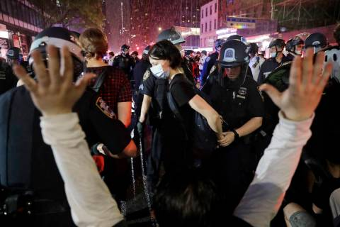 Police arrest protesters as they march through the streets of Manhattan, New York, Wednesday, J ...