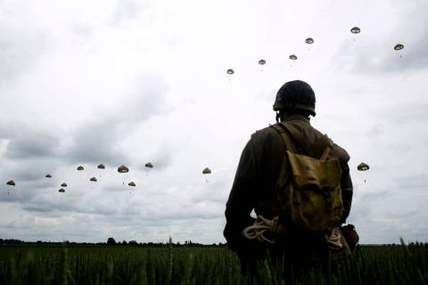 In a Wednesday, June 5, 2019, file photo, a WWII enthusiast watches French and British parachut ...