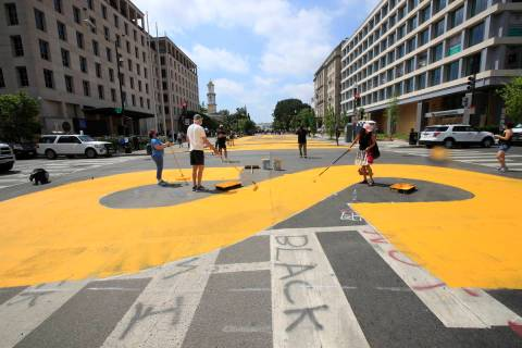 City workers and activists paint the words Black Lives Matter in enormous bright yellow letters ...