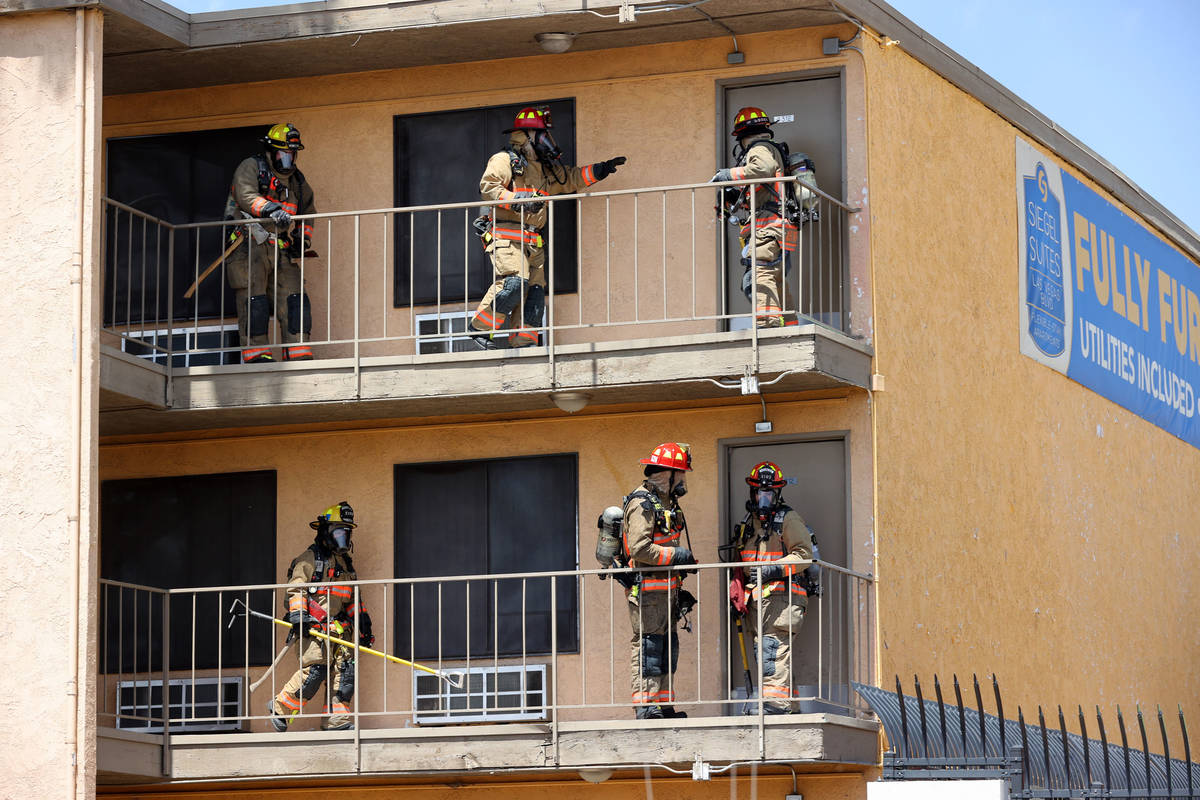 Las Vegas and Clark County firefighters check to see if residences are occupied while battling ...