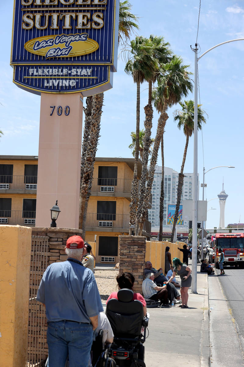Residents wait while Las Vegas and Clark County firefighters battle a fire at Siegel Suites at ...