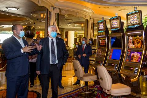Wynn Las Vegas CEO Matt Maddox talks with Gov. Steve Sisolak during a tour to view their corona ...