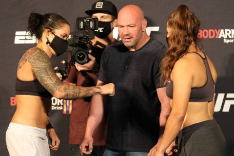UFC women's featherweight champion Amanda Nunes, left, prepares to give a fist bump to Felicia ...