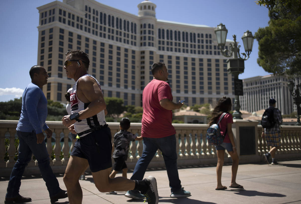 Passersby and runners move past the Bellagio on the third day that the Strip has been reopened ...
