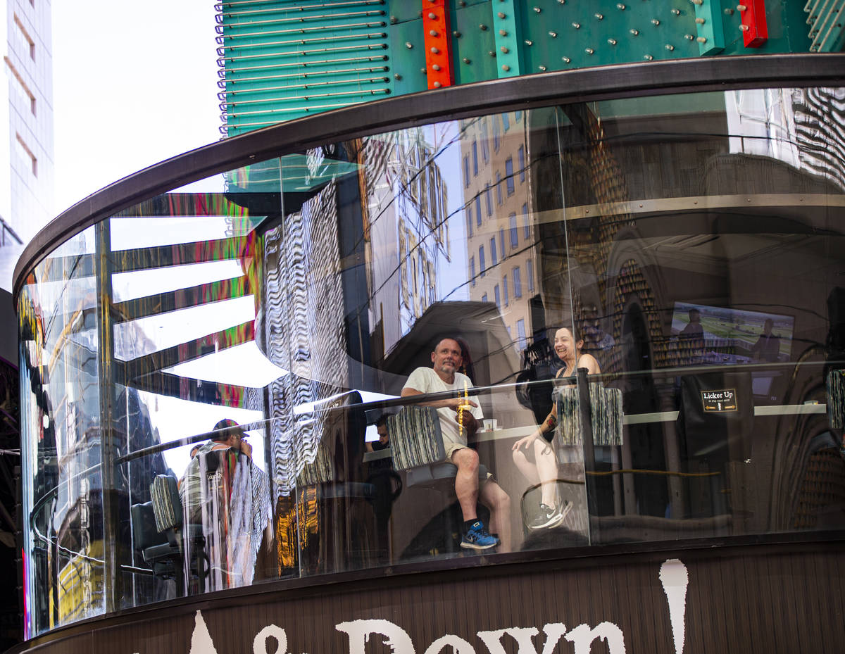 People take in the sights from the Whiskey Licker Up Saloon at the Fremont Street Experience in ...