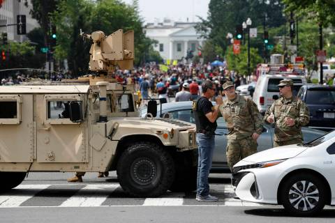 A checkpoint blocks traffic on 16th Street Northwest as people gather near the White House, Sat ...