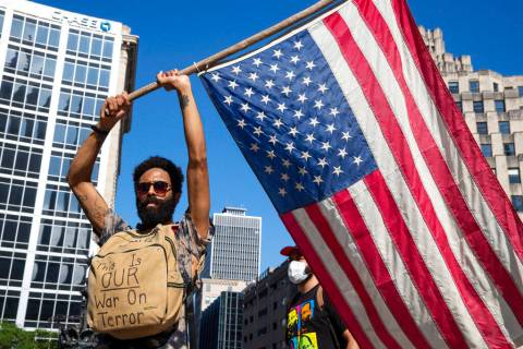 A protester holds a flag at Monument Circle following a non-violent sit-in at the Statehouse in ...