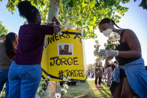 Protesters place flowers around a poster of a man killed by police during a press conference ho ...