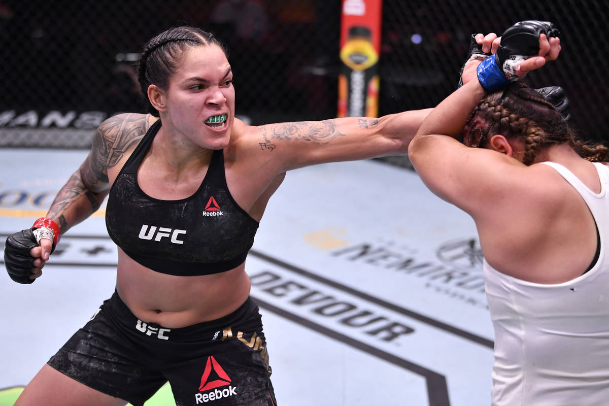 Amanda Nunes, left, of Brazil punches Felicia Spencer of Canada in their featherweight champion ...