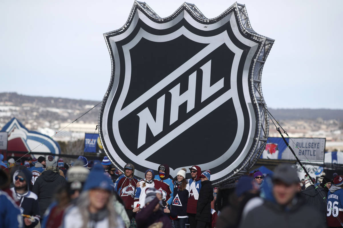 FILE - In this Saturday, Feb. 15, 2020, file photo, fans pose below the NHL league logo at a di ...