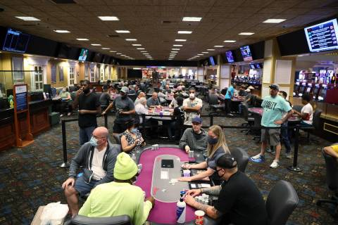 People play poker during the first day of reopening at The Orleans hotel-casino in Las Vegas, T ...
