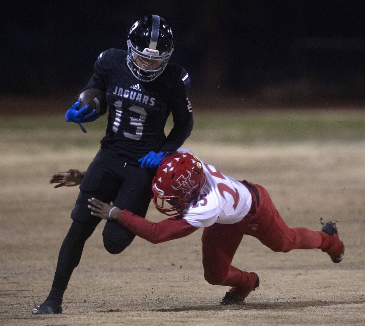 Desert Pines' Michael Jackson (13) runs with the ball as Arbor View's Adrian Bates (25) jumps t ...
