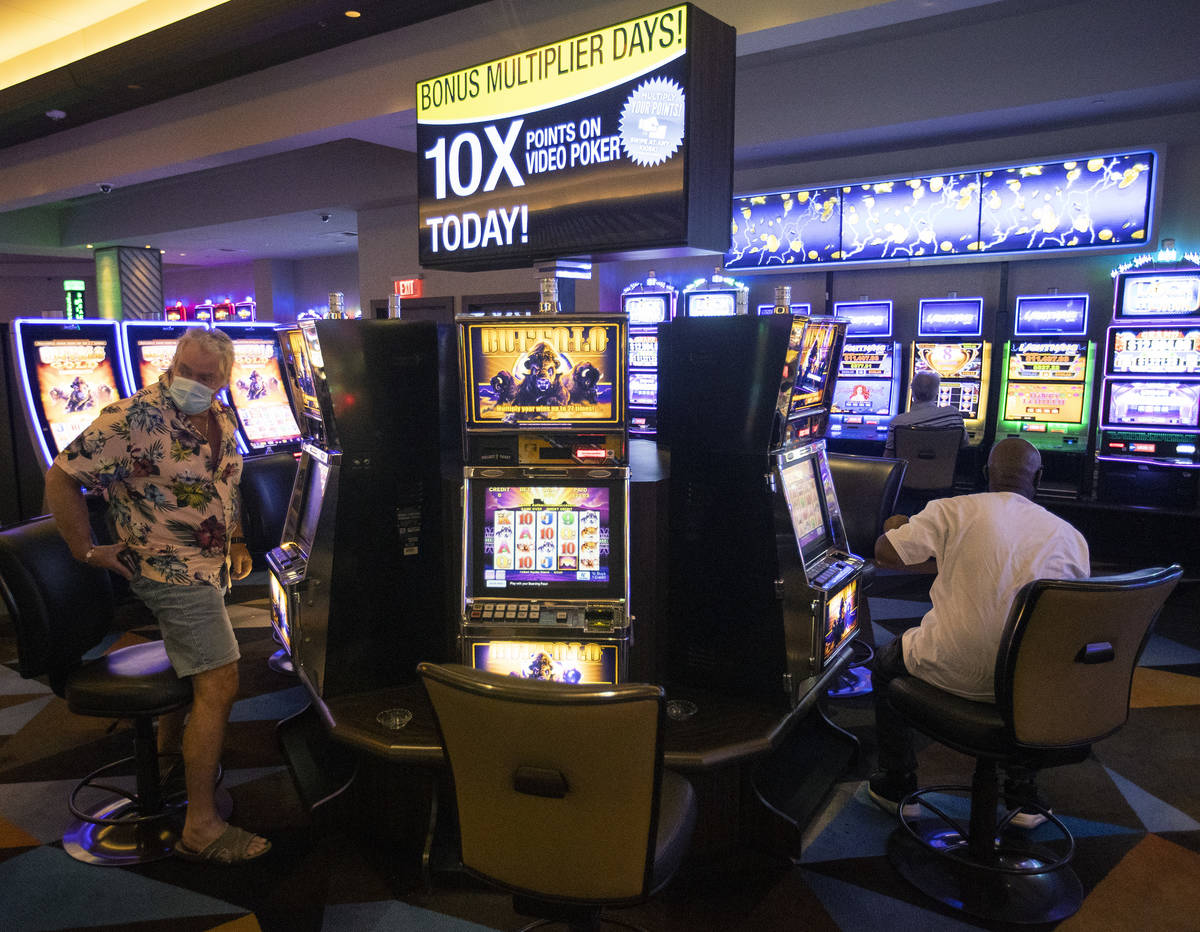 The casino floor has gamblers playing one seat apart to maintain social distance and slow the s ...