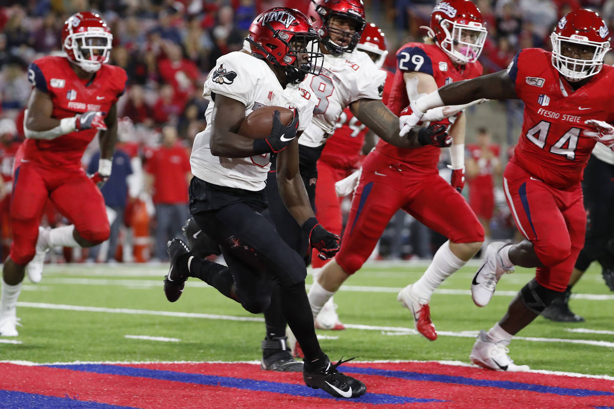 UNLV running back Charles Williams tries to get around Fresno State defensive lineman Leevel Ta ...