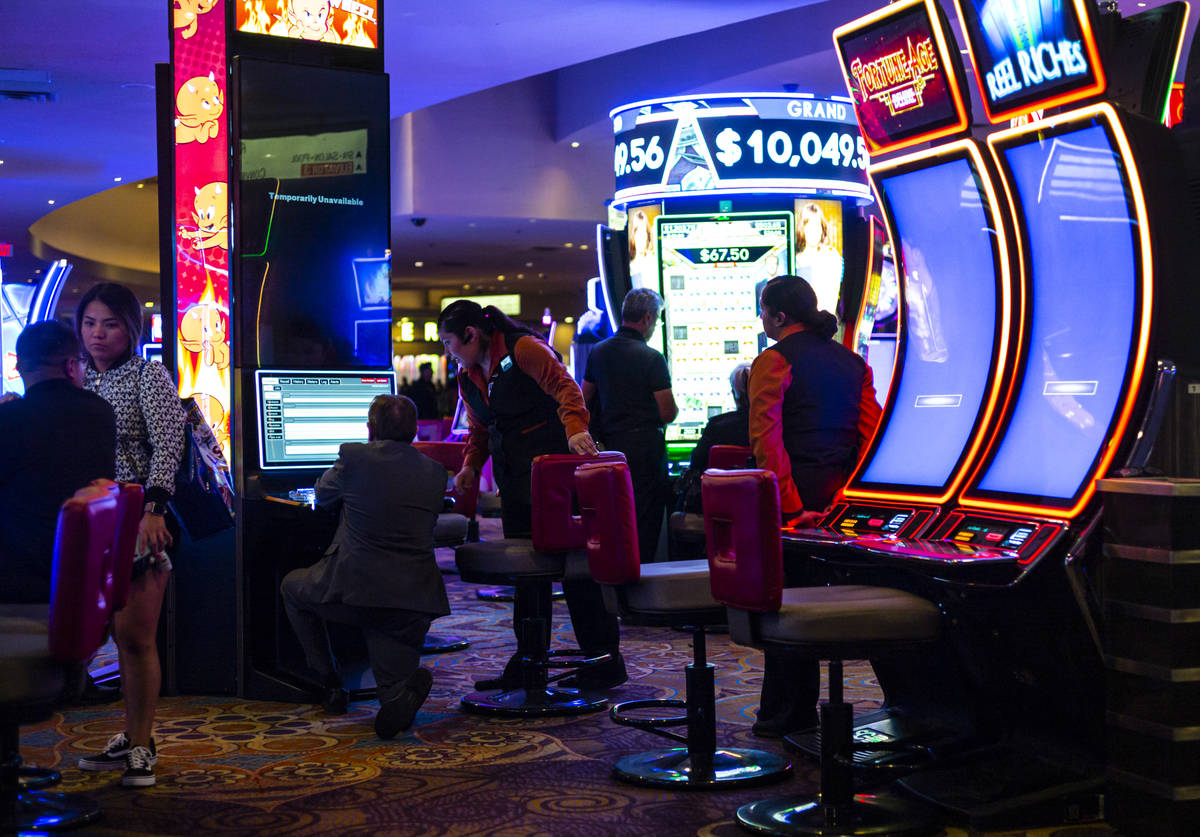 Slot attendants help shut down machines shortly before midnight at the Luxor in Las Vegas on Mo ...
