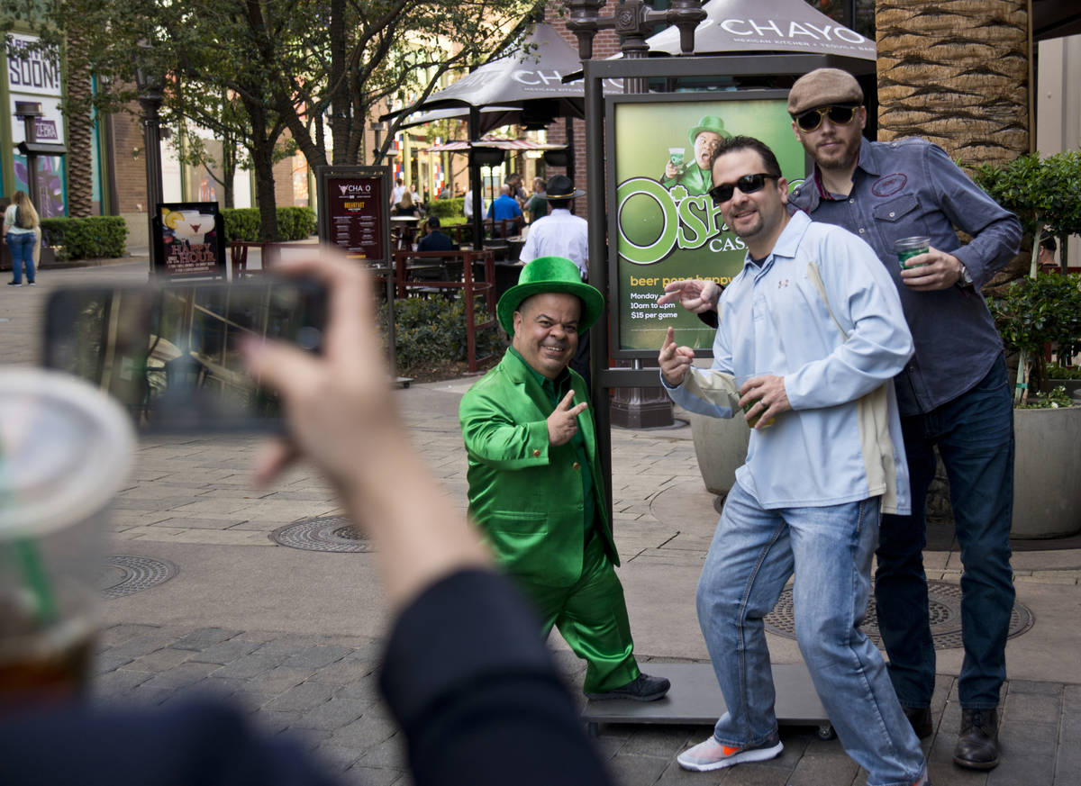 Brian Thomas, O'Sheas Casino manager and resident leprechaun, left, takes a photo with brothers ...