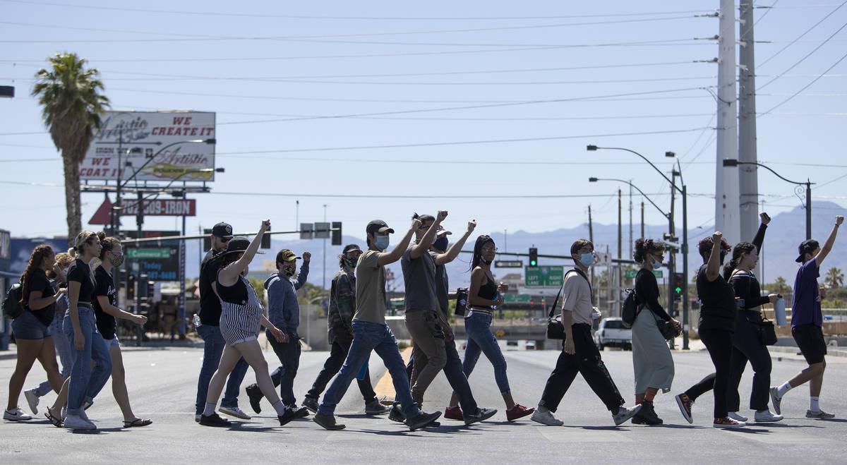 Demonstrators cross Charleston Boulevard on their way to Las Vegas City Hall in an effort to de ...