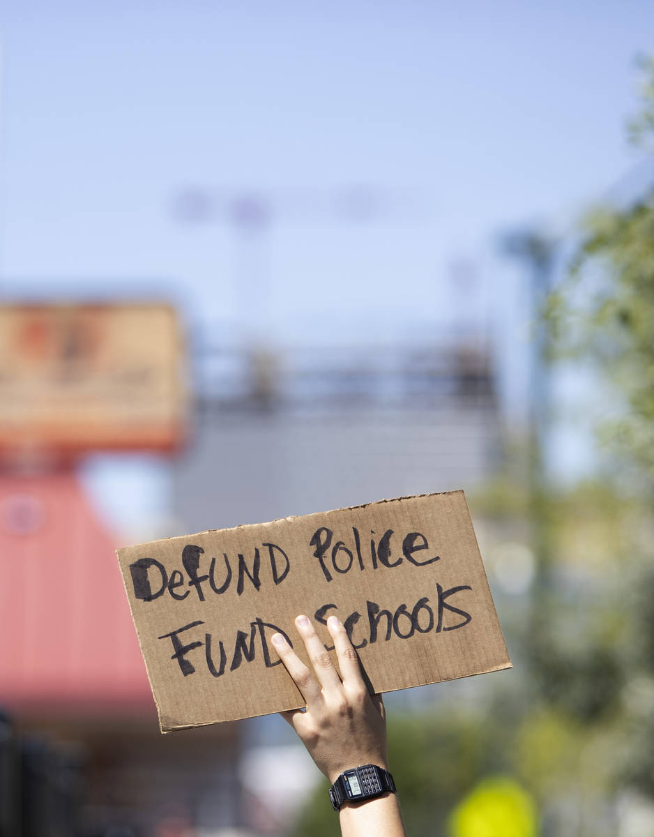 One marcher carries a sign calling for local politicians to defund police and fun schools on We ...