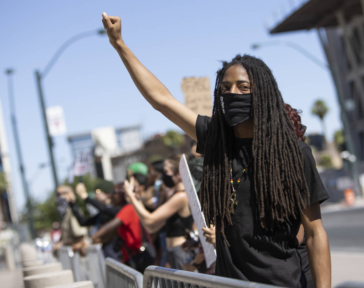 """Dre Thurman holds his fist high as other protesters chant """"no justice, no peace"""" outs ..."""
