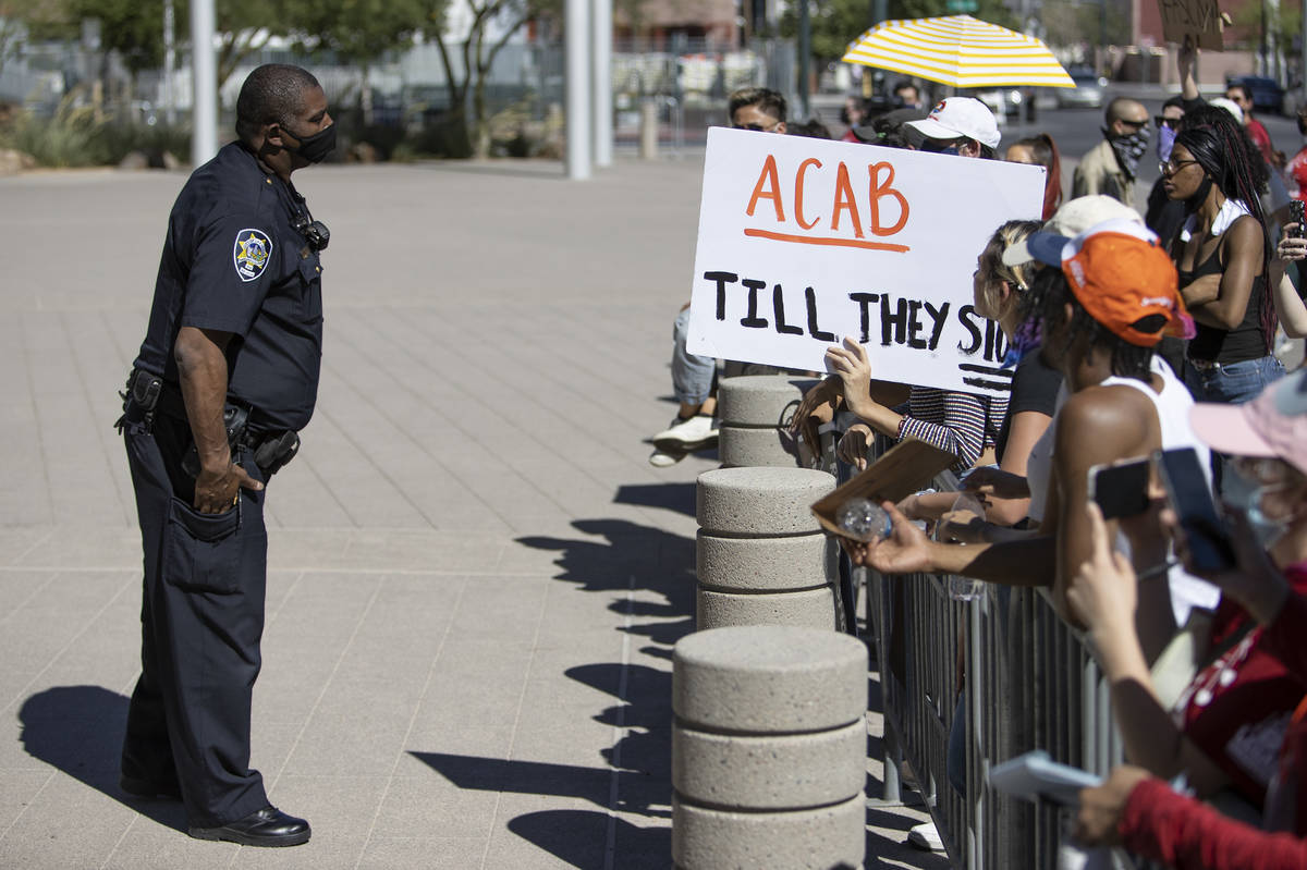 A Las Vegas police officer asks protesters, who asked to see Mayor Goodman to discuss defunding ...