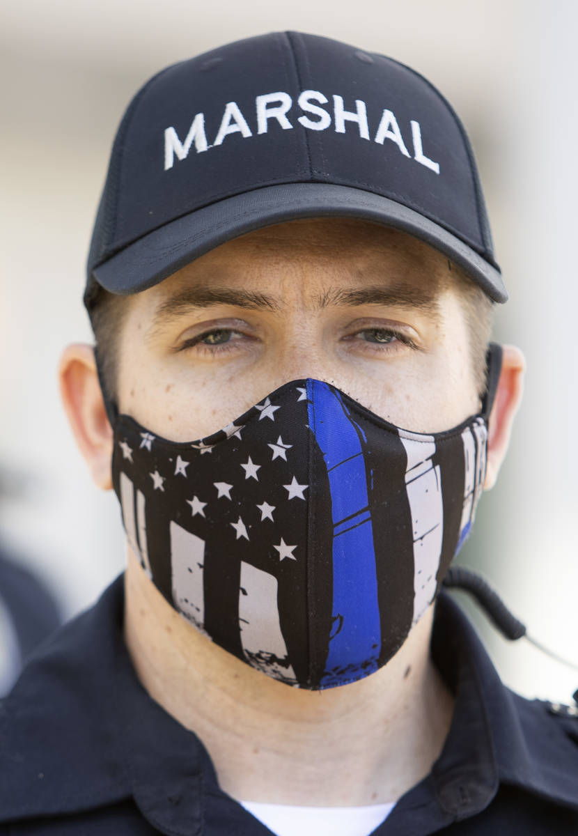 """One Las Vegas police officer wears a """"thin blue line"""" mask while standing between pro ..."""