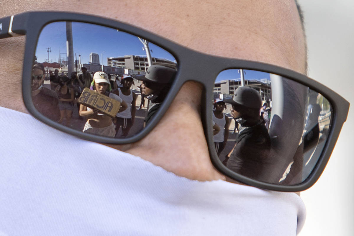 Demonstrators are reflected in the sunglasses of a Las Vegas police officer outside Las Vegas C ...
