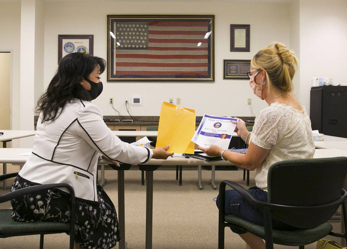 Stacey Campbell, left, chief deputy clerk at the City of Las Vegas, hands out the 2020 recall g ...