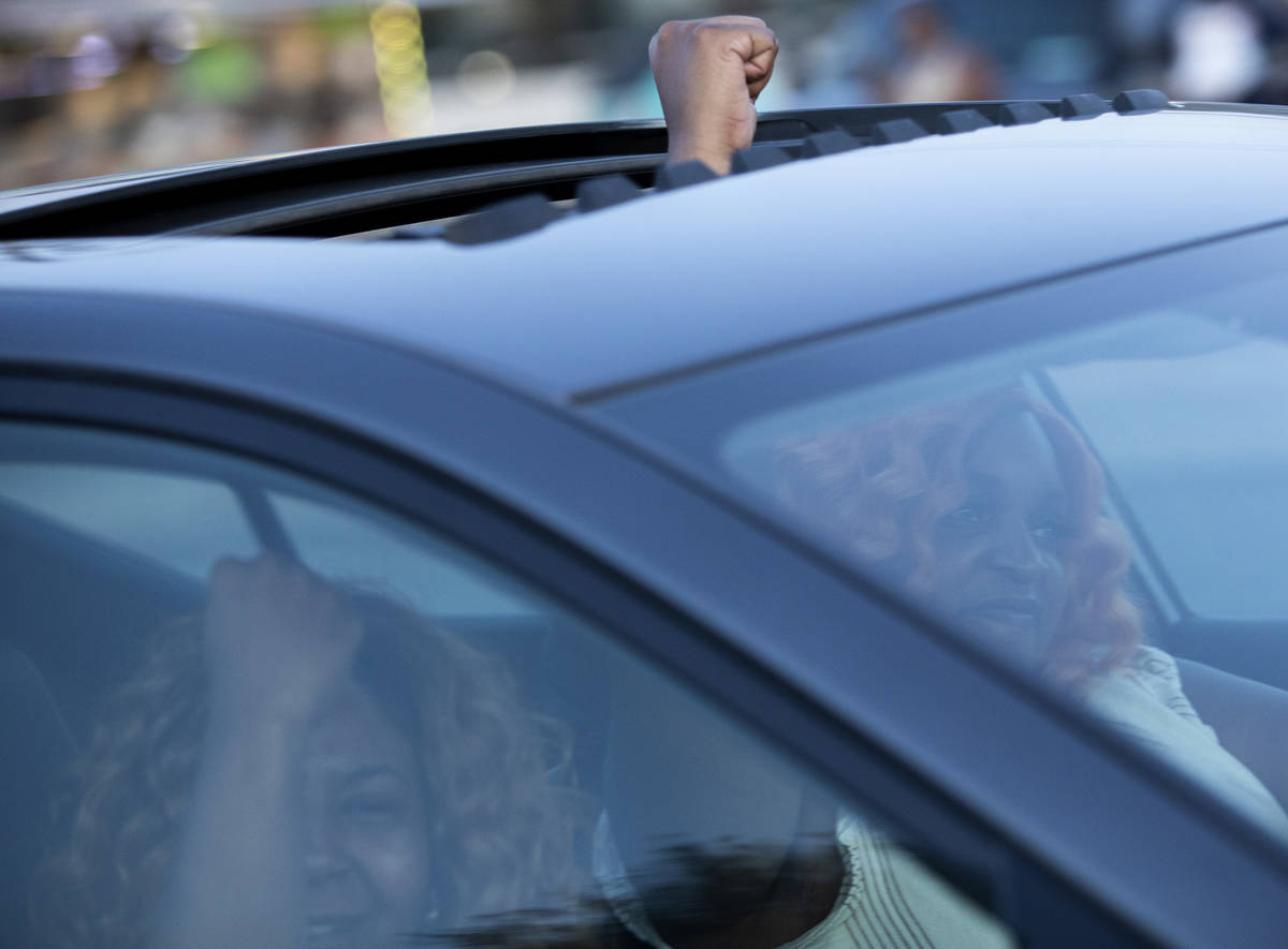 A vehicle cheers as it passes a protest against police brutality that marched from Molasky Fami ...