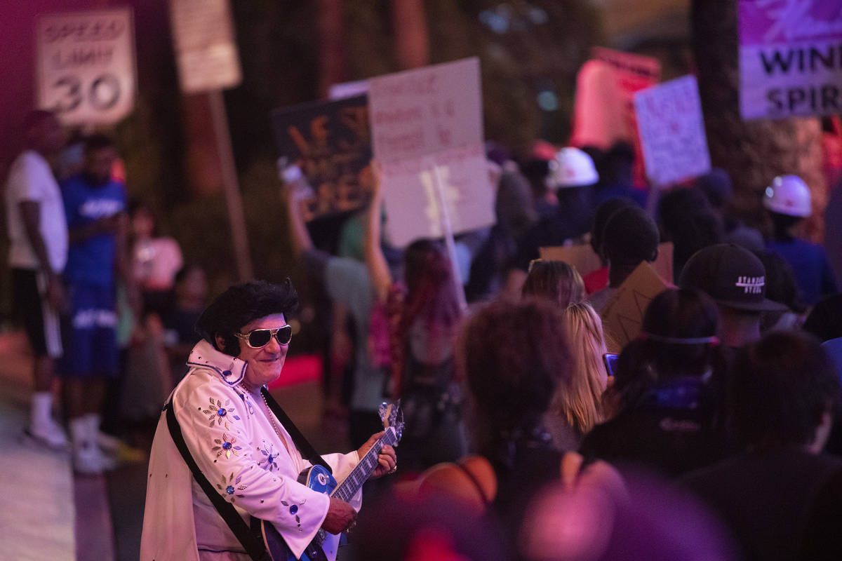 An Elvis impersonator interacts with protesters as they pass by during a protest against police ...
