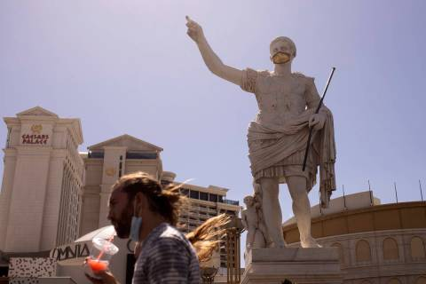 Pedestrians walk past a masked statue in front of Caesars Palace on the third day that the Stri ...