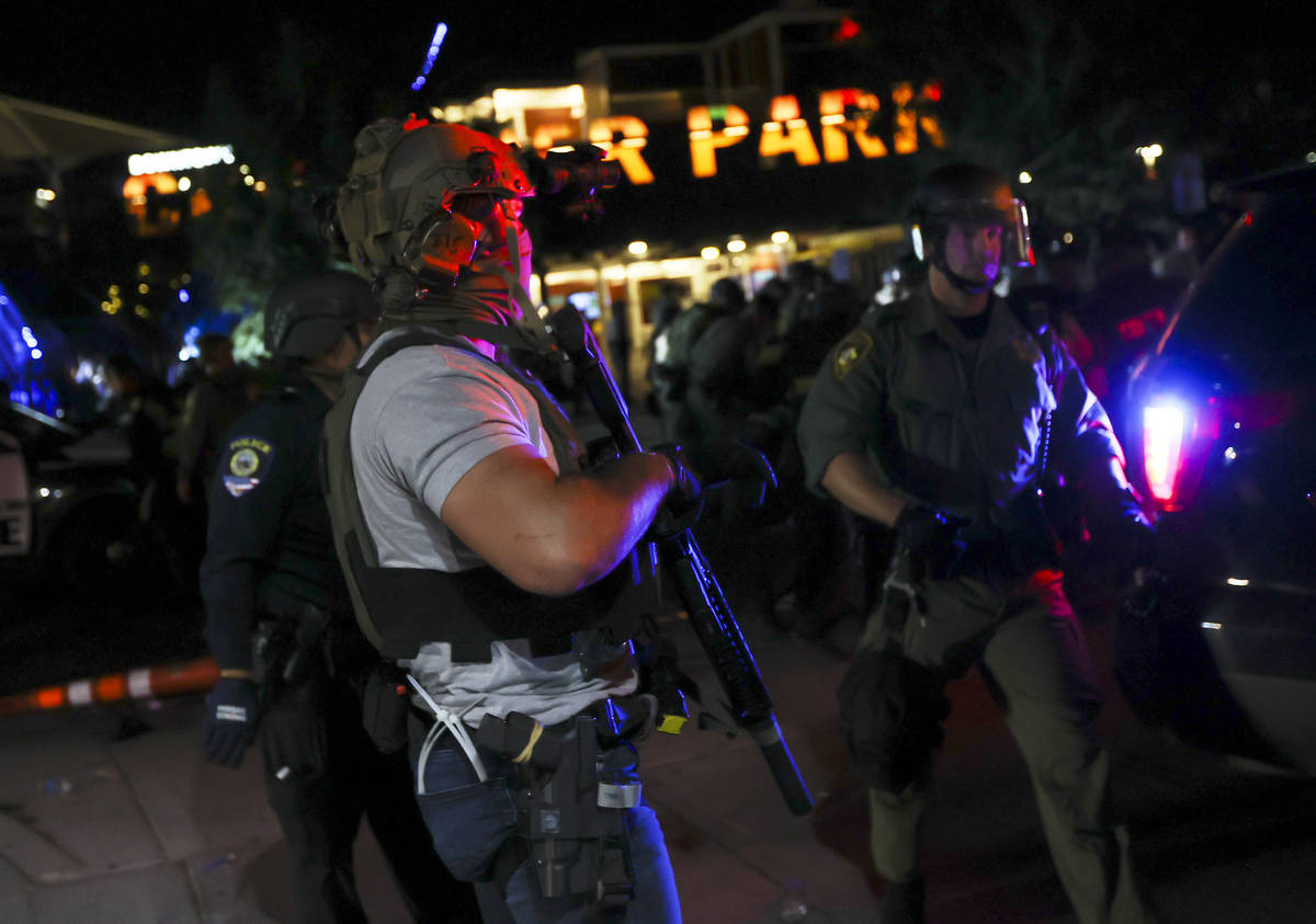 A man who appears to be impersonating a federal agent stands among Las Vegas police officers du ...