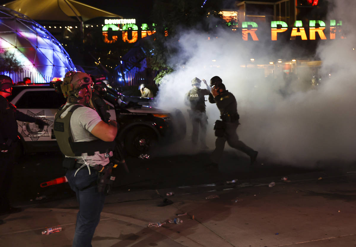 A man who appears to be impersonating a federal agent, left, stands among Las Vegas police offi ...