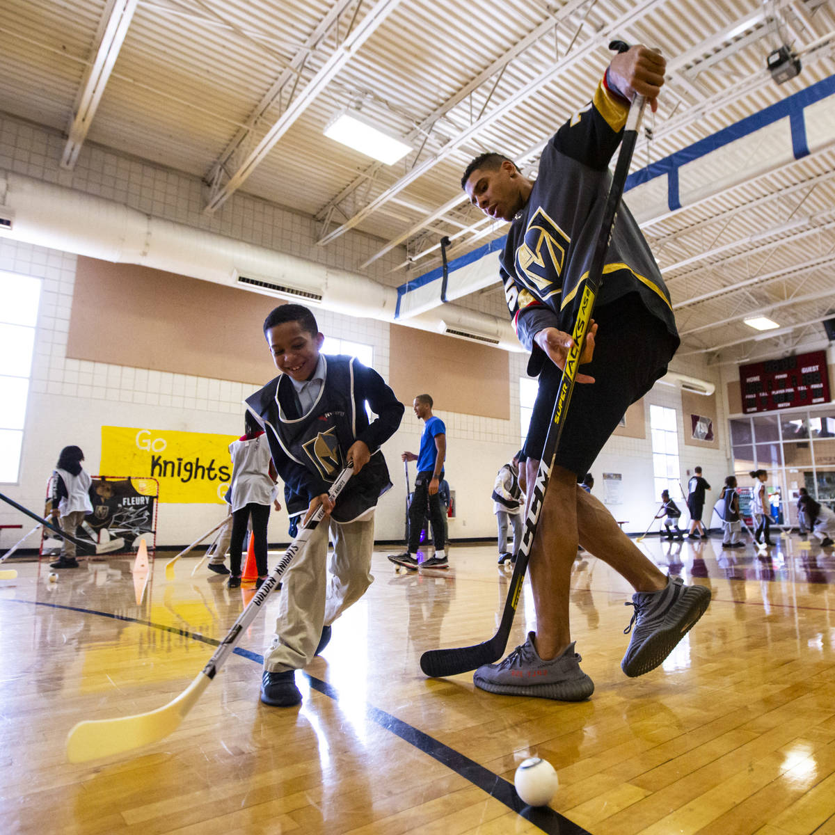 Eight-year-old Desmond Hester, left, plays with Golden Knights forward Ryan Reaves during a you ...