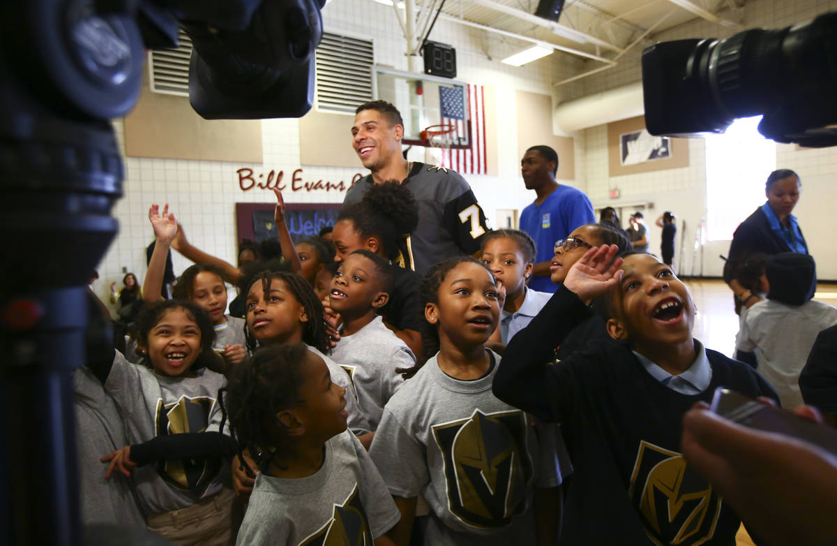 Golden Knights forward Ryan Reaves is surrounded by children during a youth street hockey clini ...