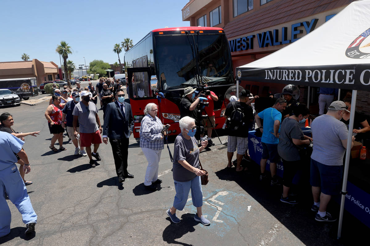 People line up to T-shirts during a fundraiser for Las Vegas police officer Shay Mikalonis at S ...