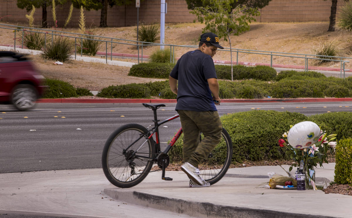 An unidentified cyclist walks by a small memorial near where two teen brothers were killed in a ...