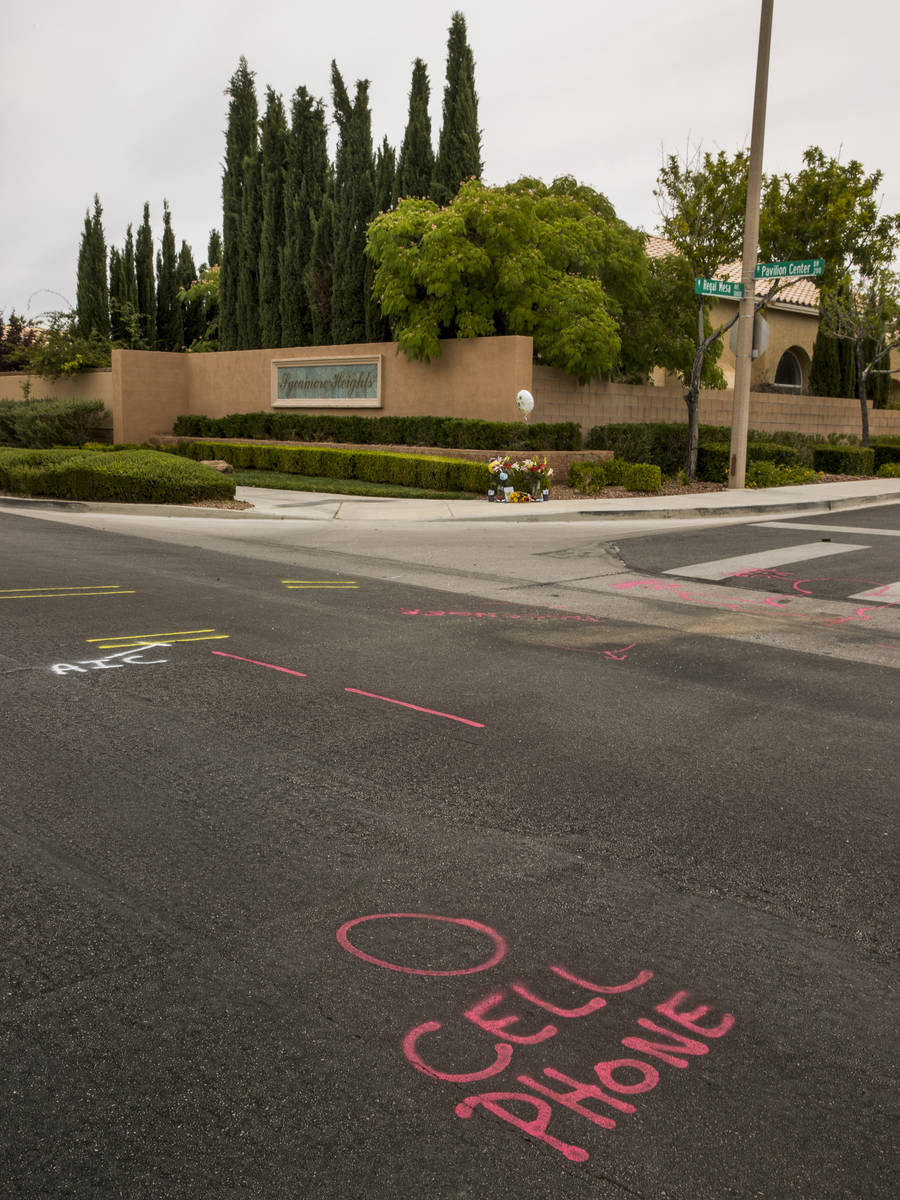 Police spray paint outlines a cell phone spot on the road mark where two teen brothers were kil ...