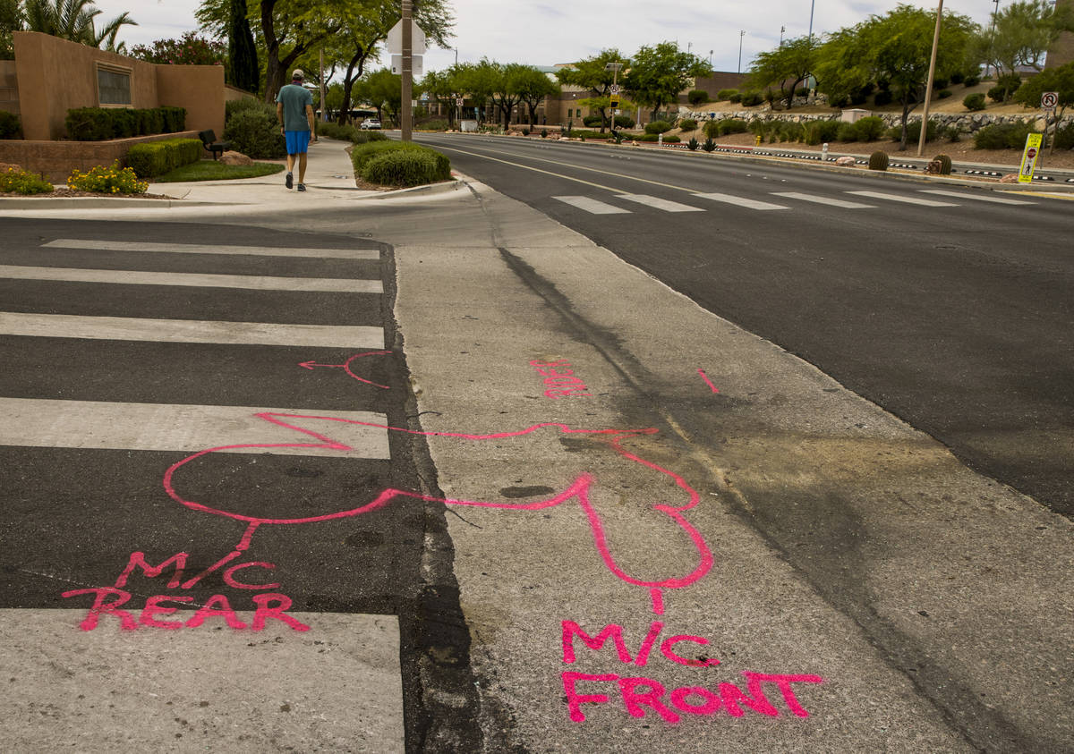 Police spray paint outlines on the road mark where two teen brothers were killed in a recent mo ...