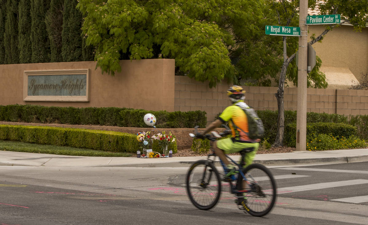 A cyclist looks to a small memorial near where two teen brothers were killed in a recent motorc ...