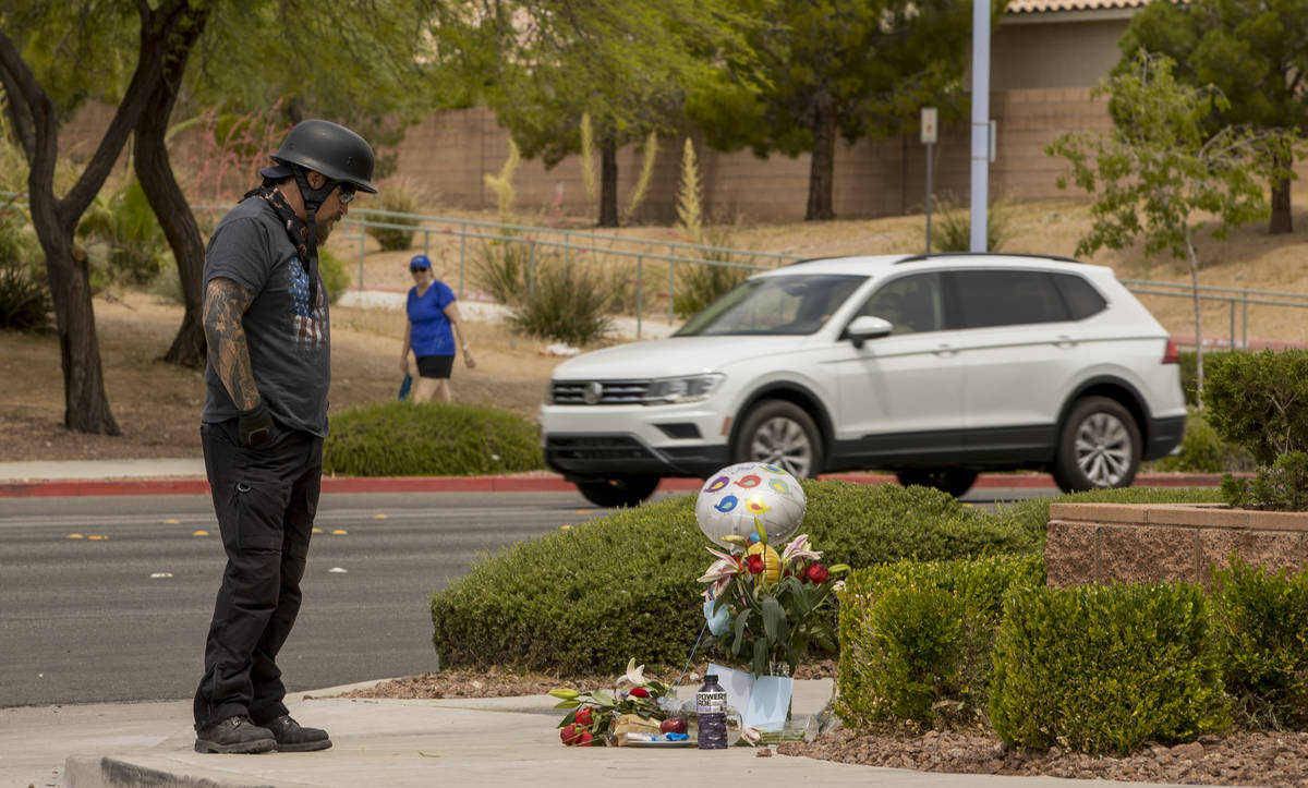 Motorcyclist Doug Durbin stops by a small memorial near where two teen brothers were killed in ...