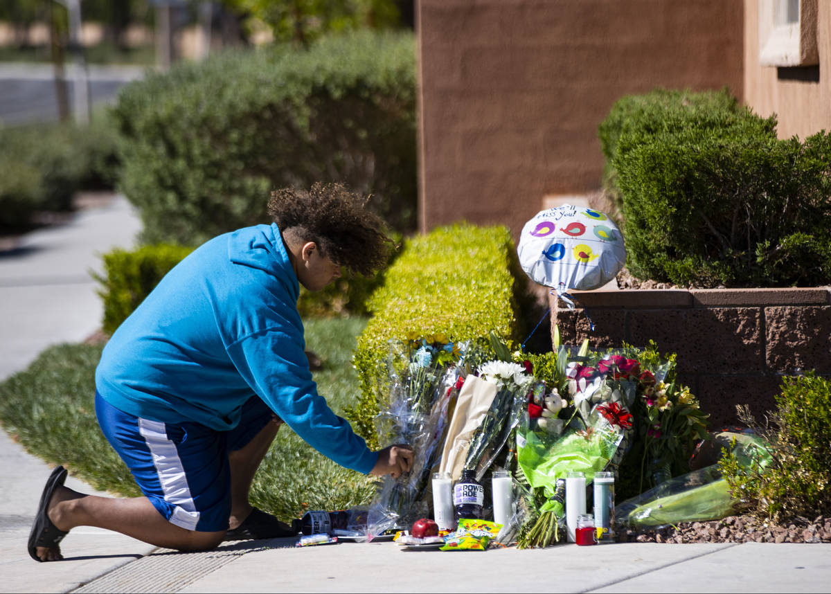 John Taylor, 14, helps arrange items left at the memorial left for David Cox, 18, and Brandon C ...